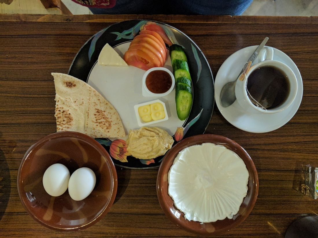 A common vegetarian breakfast in Jordan - pita bread, yogurt, hummus, salad, cheese and black tea.