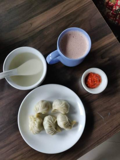 Butter tea along with steamed momos and spicy dip.