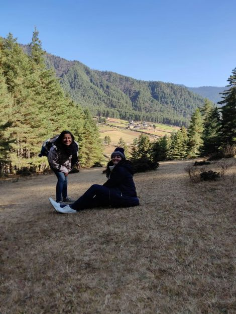 two girls sitting a top a hill in Haa Valley Bhutan (Gangtey Bhutan)